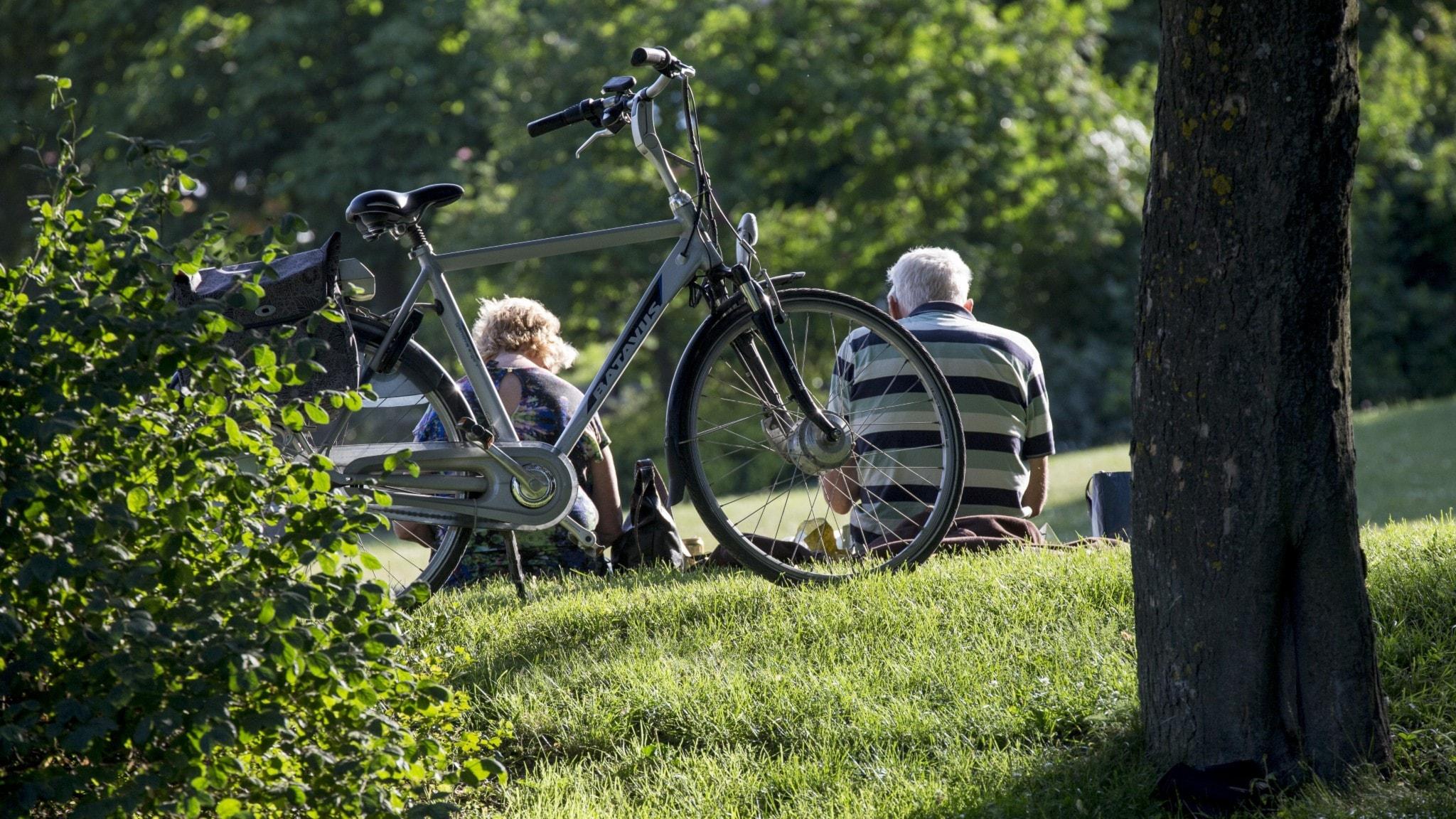 Två personer och en cykel i gräset.