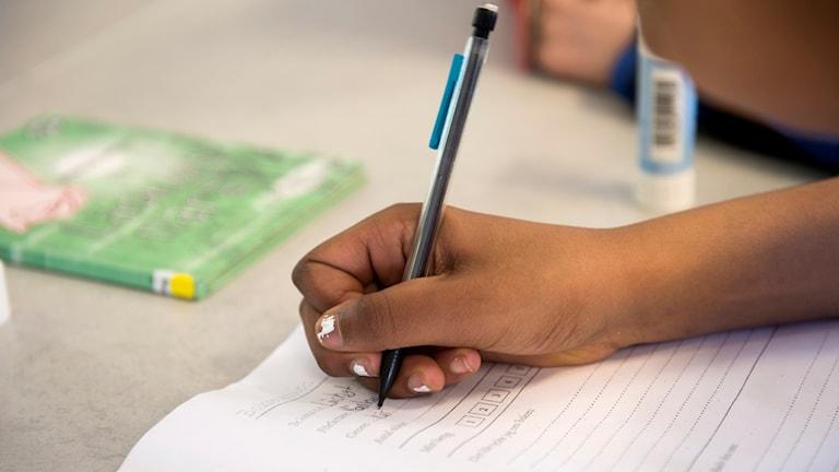 Elev som skriver under en svenska lektion.