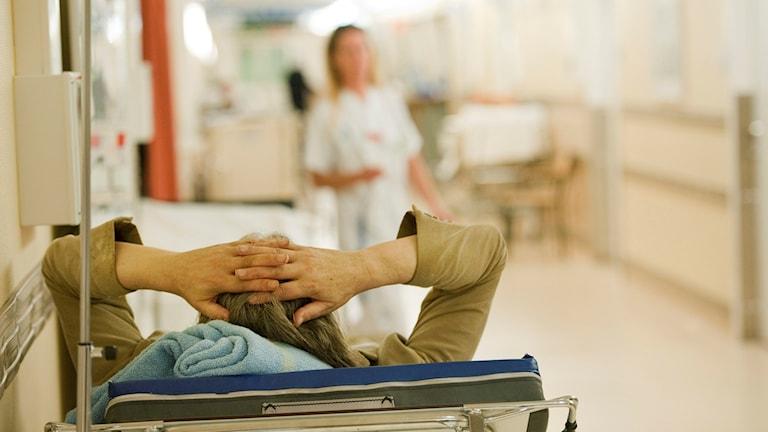 En patient ligger i en säng i en korridor på akuten på Södersjukhuset.