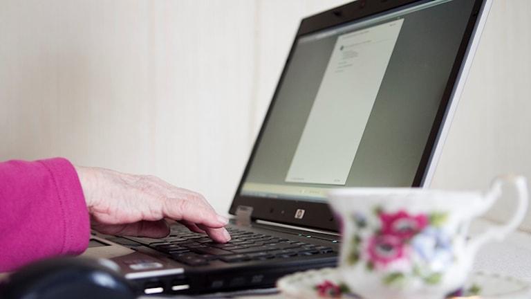 En äldre kvinna sitter vid en laptop och surfar på internet.