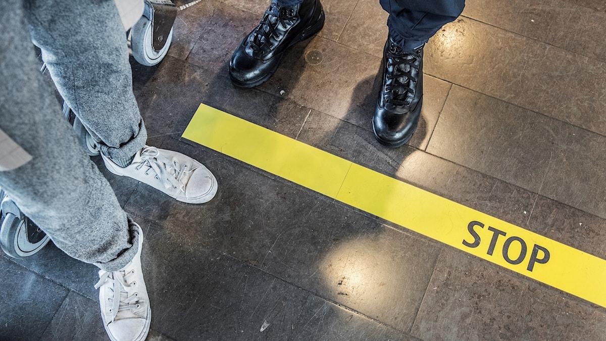 """Två personer står på varsin sida om ett märke på golvet som det står """"stopp"""" på."""