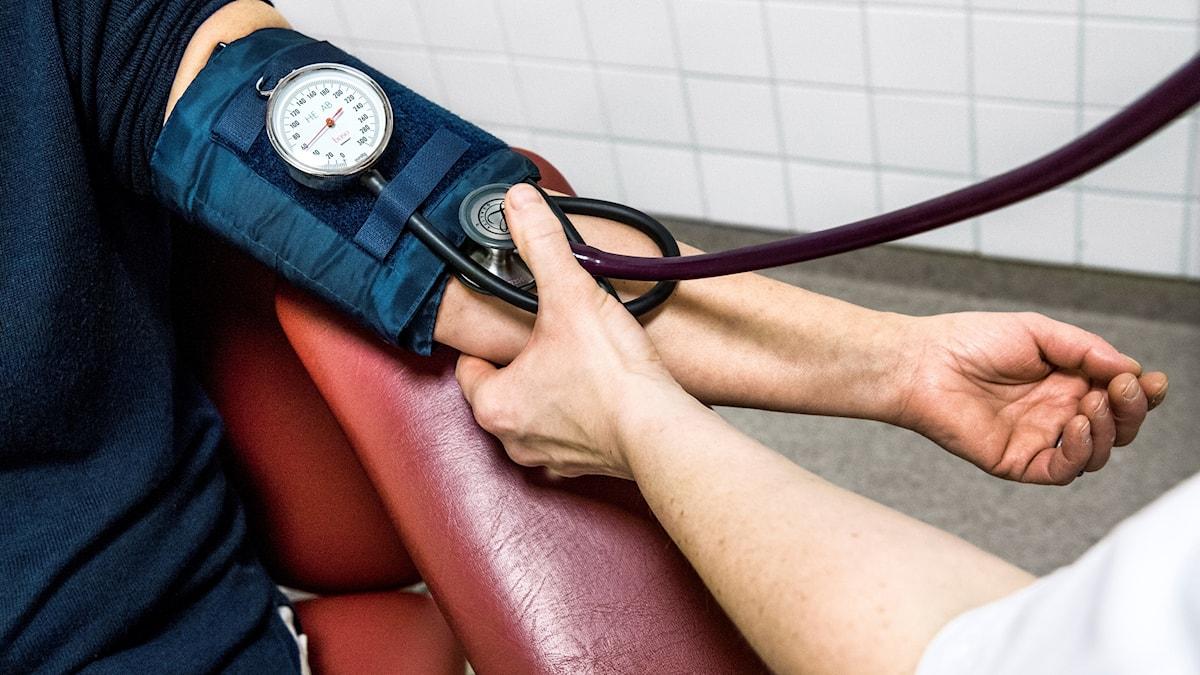 Närbild på en sjuksköterska som mäter blodtryck på en patient.