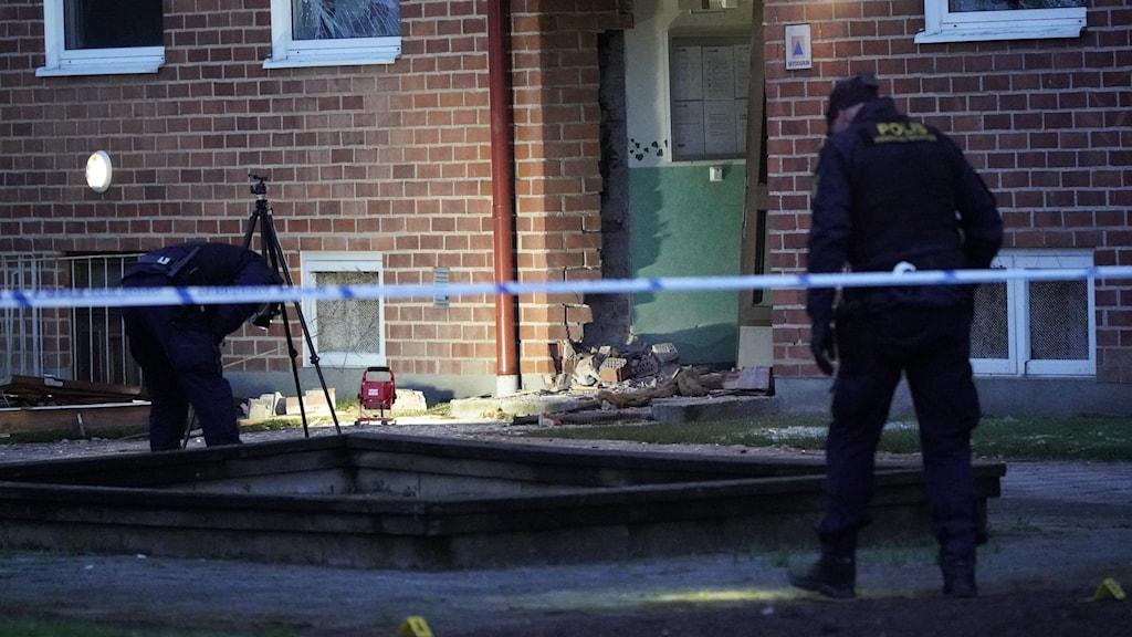 Bild på poliser utanför en port till ett lägenhetshus. Porten och flera fönster är förstörda.
