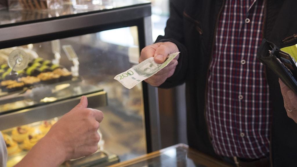 En man betalar med en sedel.