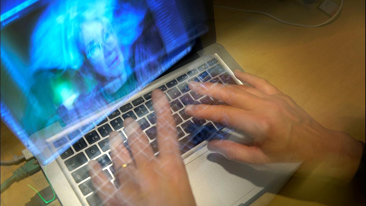 En kvinna skriver snabbt på sin dator.