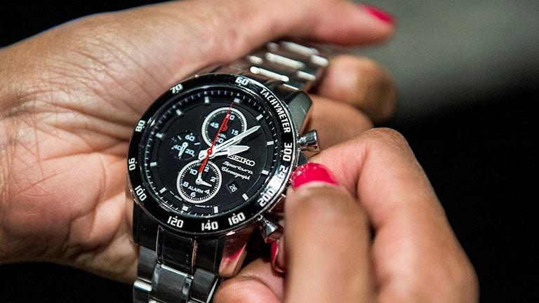 En kvinna ställer om sin armbandsklocka.