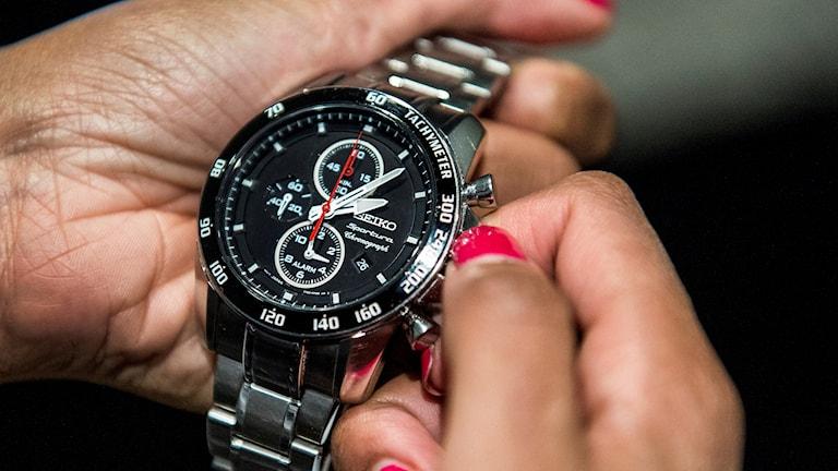 En kvinna ställer om sin klocka.
