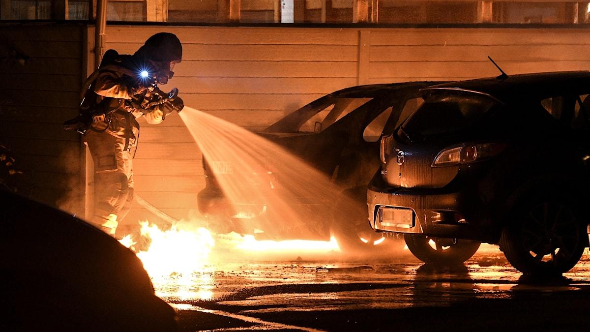 Räddningstjänsten släcker en brinnande bil.