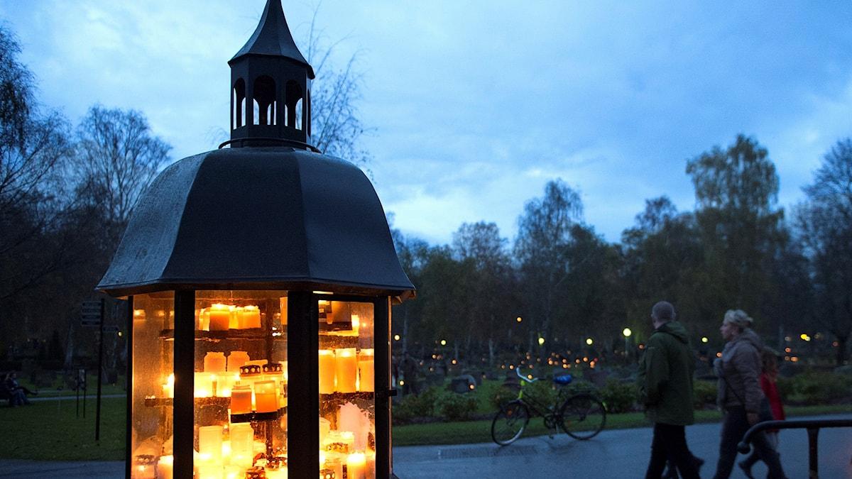Tända ljus på Solna kyrkogård norr om Stockholm på Alla helgons dag.