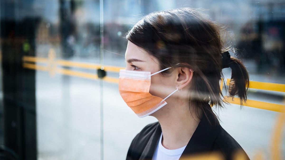 En tjej med munskydd väntar på bussen.