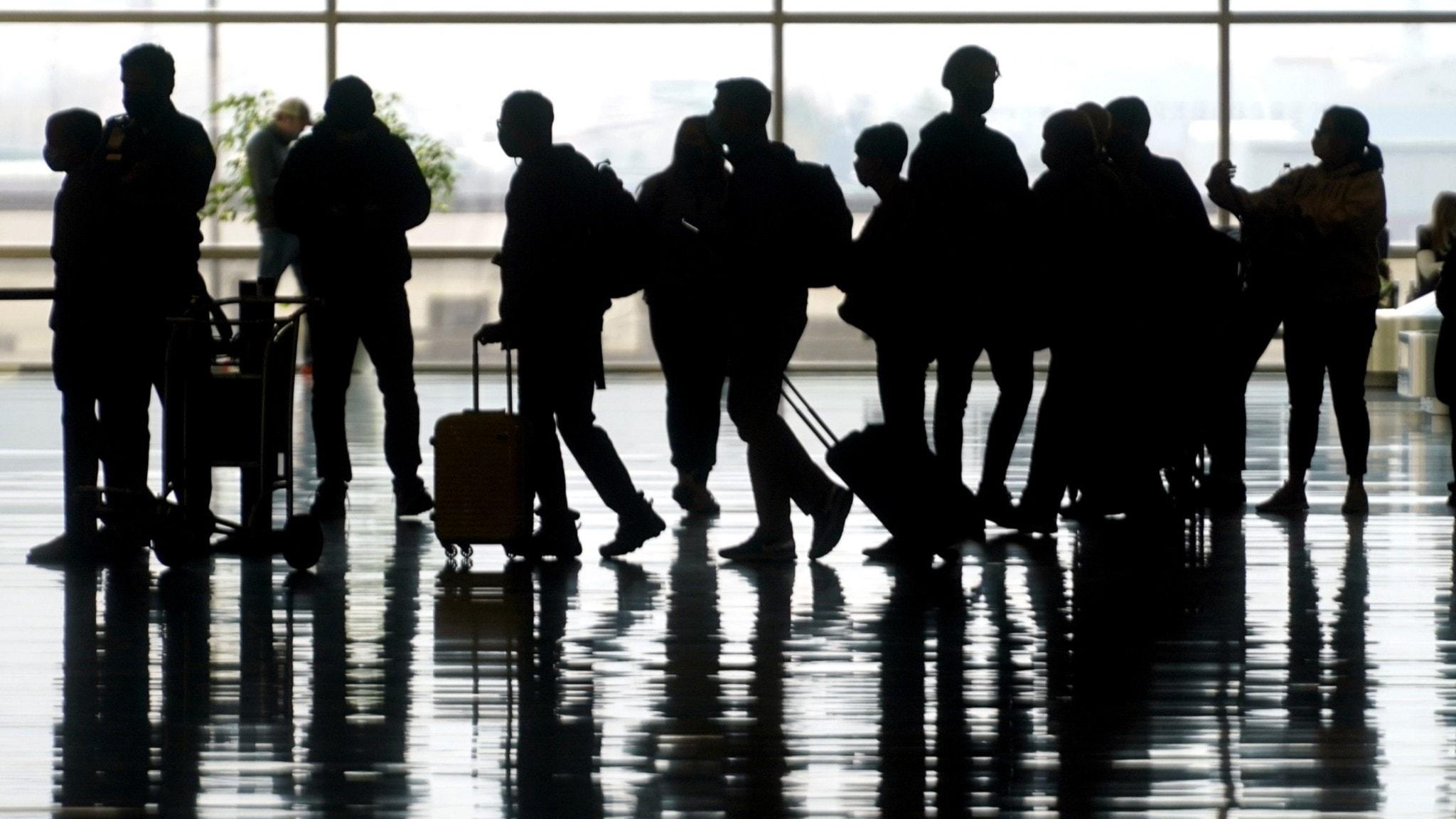 Bild på flera personer som rullar sina resväskor på en flygplats.