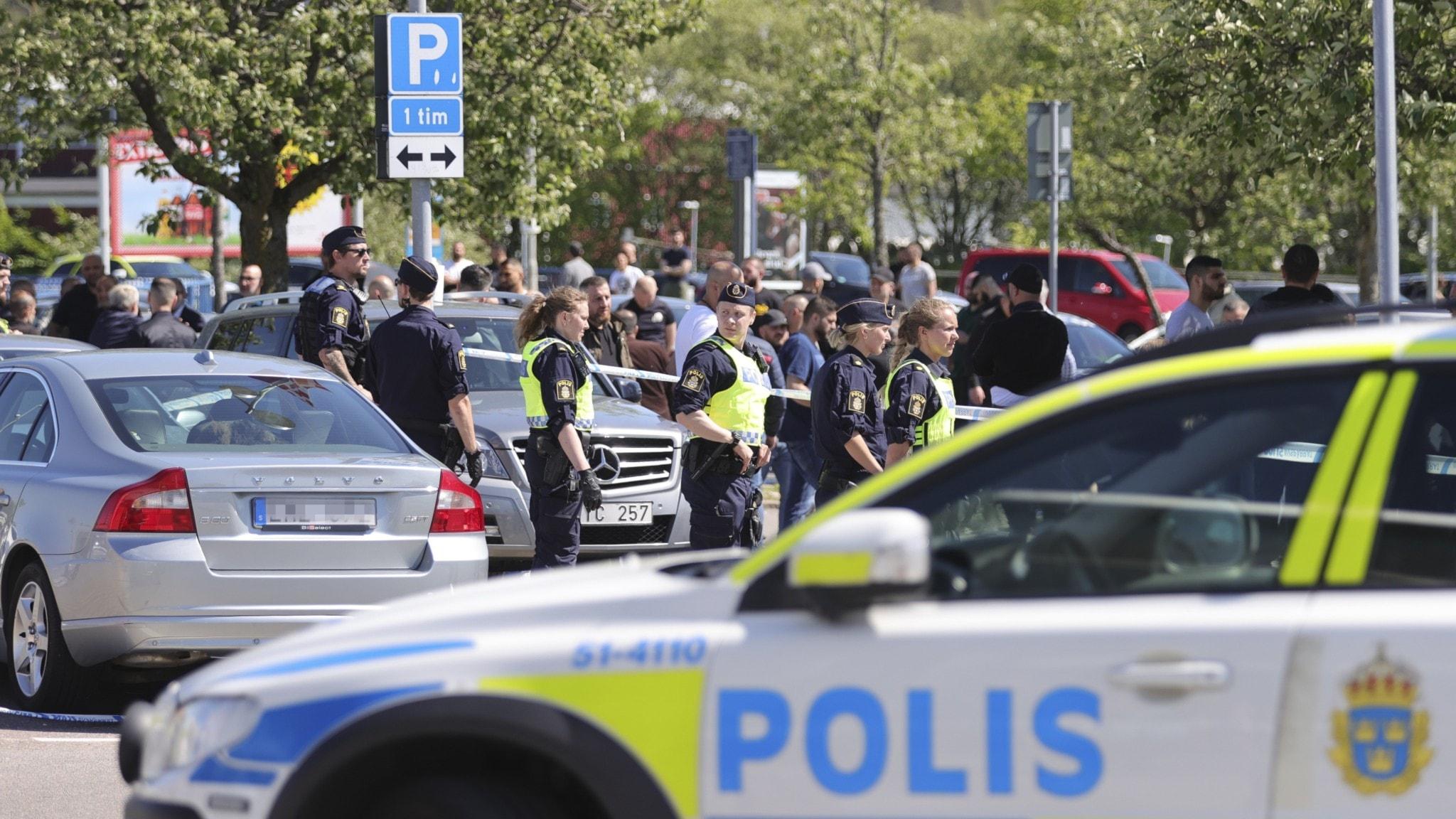 Poliser och polisbilar på torget i Hjällbo.