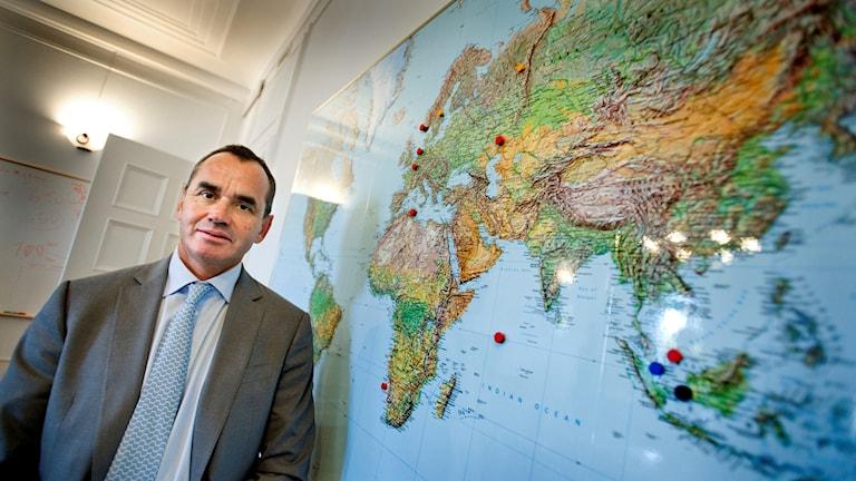 Ian Lundin, styrelseordförande för Lundin Petroleum, står framför en karta.