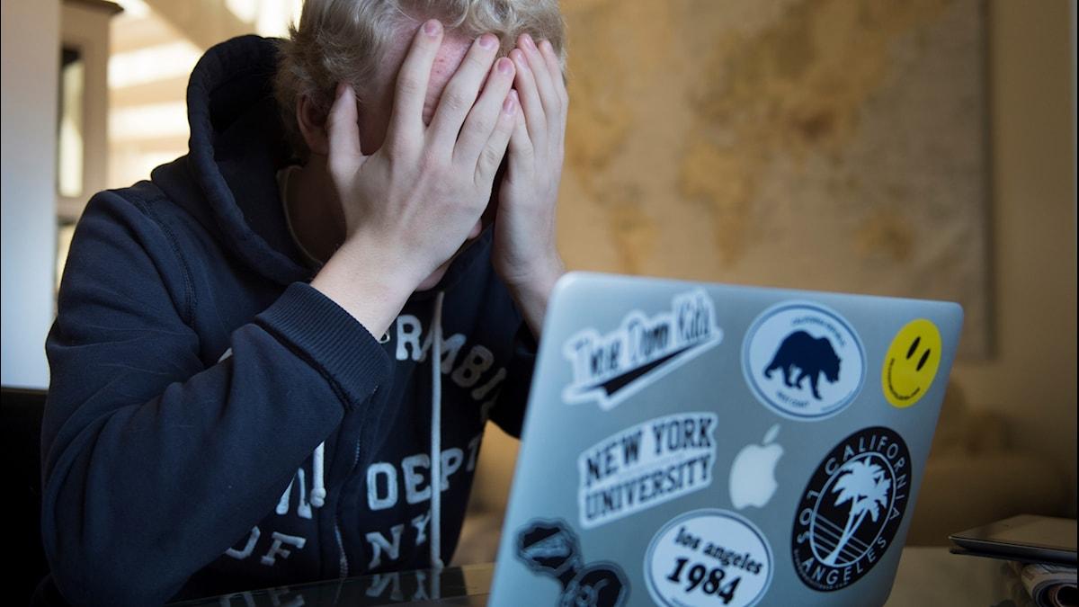 En tonåring som utsatts för nätmobbning gömmer ansiktet i händerna  framför sin dator