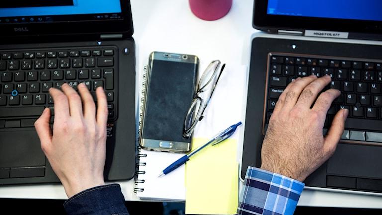 En kvinnlig hand och en manlig hand som arbetar med bärbara datorer.