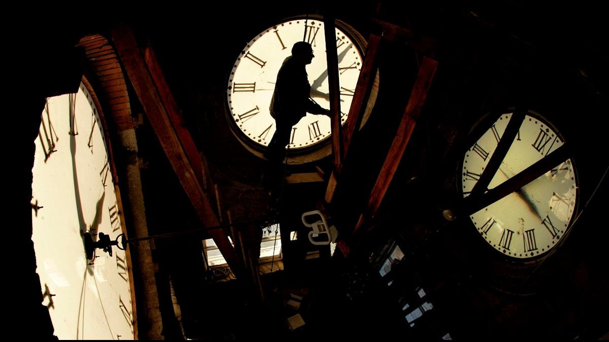 En man ställer om många klockor.