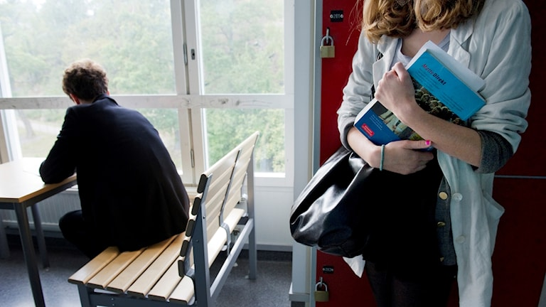 Två skolelever, en flicka och en pojke, i en korridor på en högstadieskola