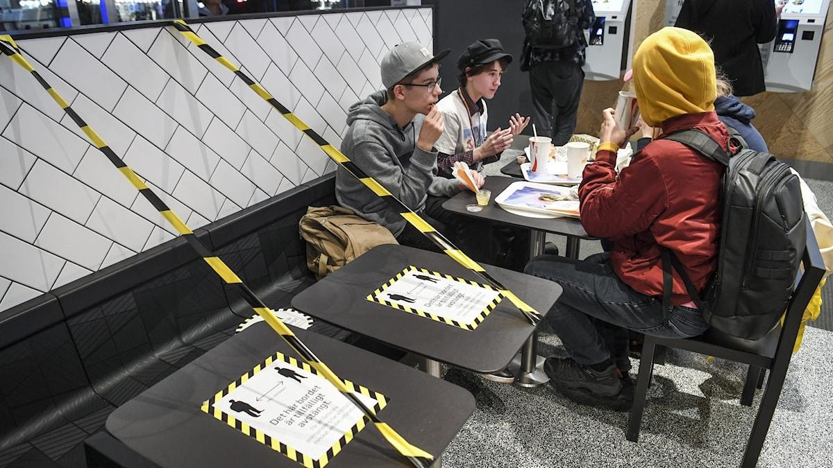 Ungdomar äter på coronasäkrad snabbmatsrestaurang.
