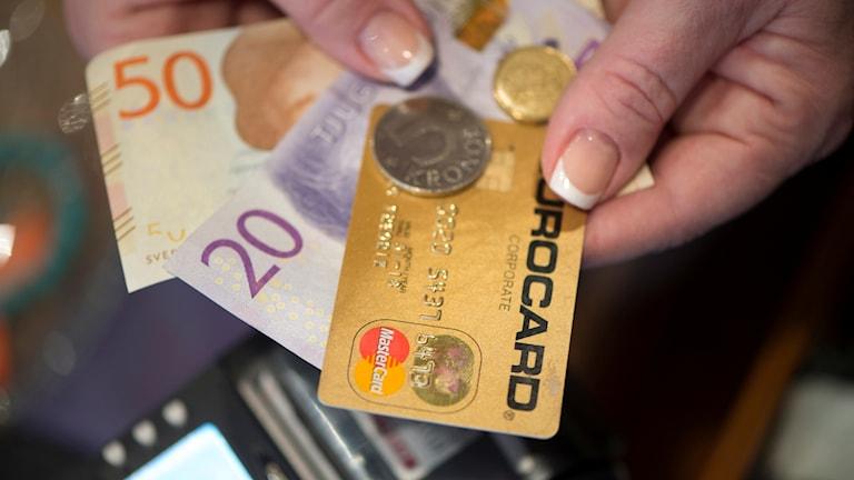 En person håller i pengar och bankkort.