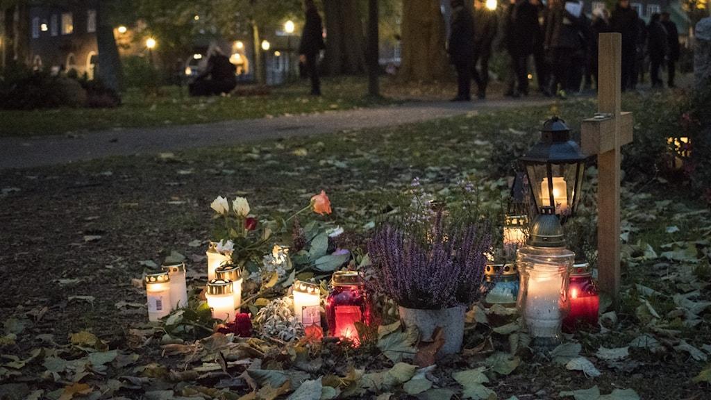 Besökare, blommor och tända ljus på Katarina kyrkogård i Stockholm under alla helgons dag.