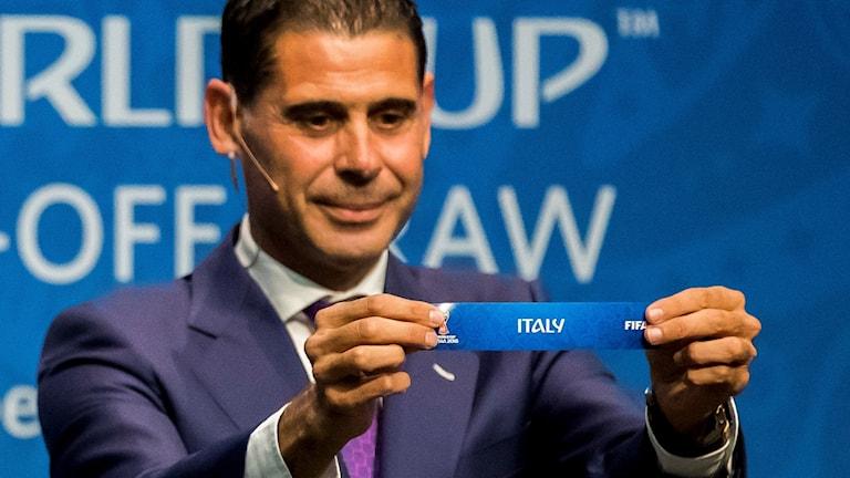 Den spanska före detta fotbollsspelaren Fernando Hierro håller upp en lapp som det står Italien på.