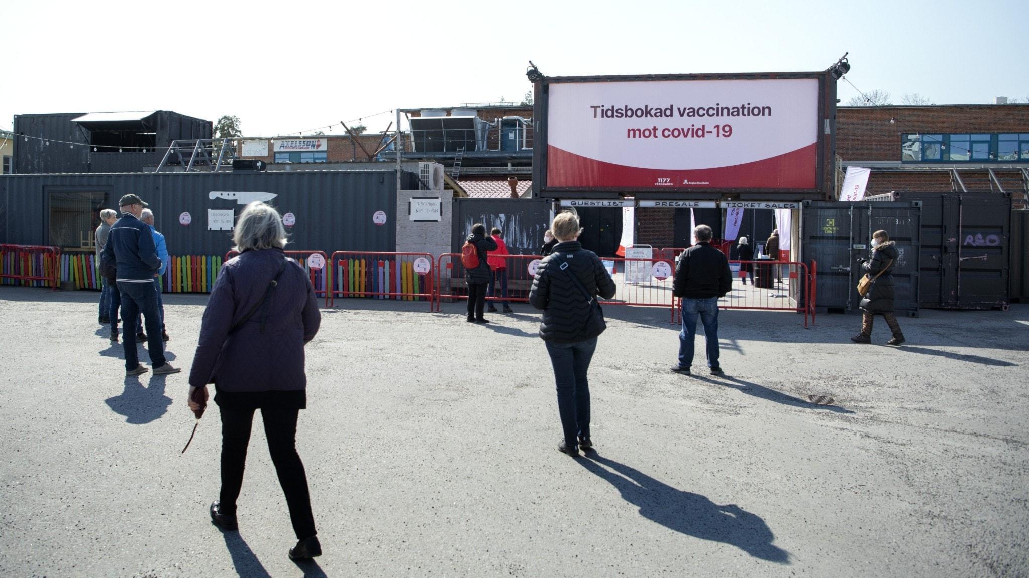 Bilden visar människor som väntar på vaccinering.