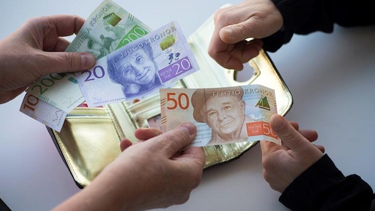 Händer som delar på pengar. Foto: Fredrik Sandberg/TT