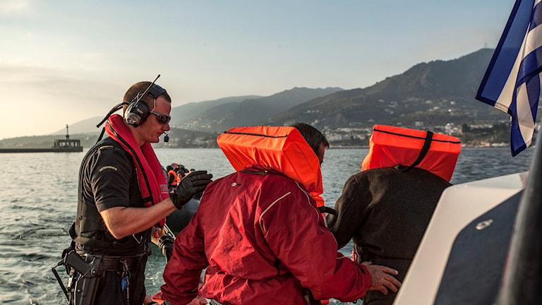 En man från Kustbevakningen hjälper två flyktingar ombord på en båt.
