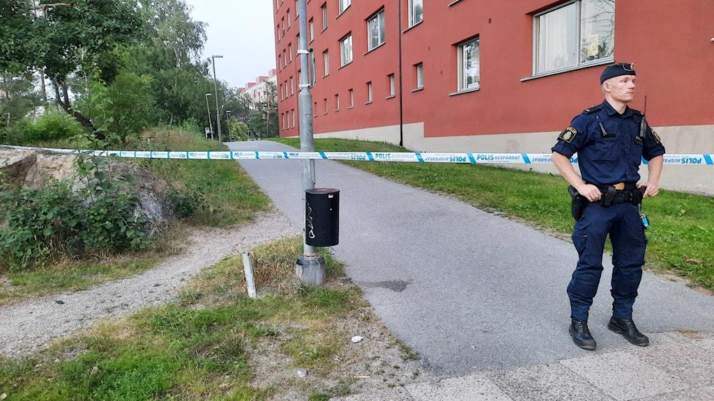 Polis framför avspärrning med blåtejp utomhus.