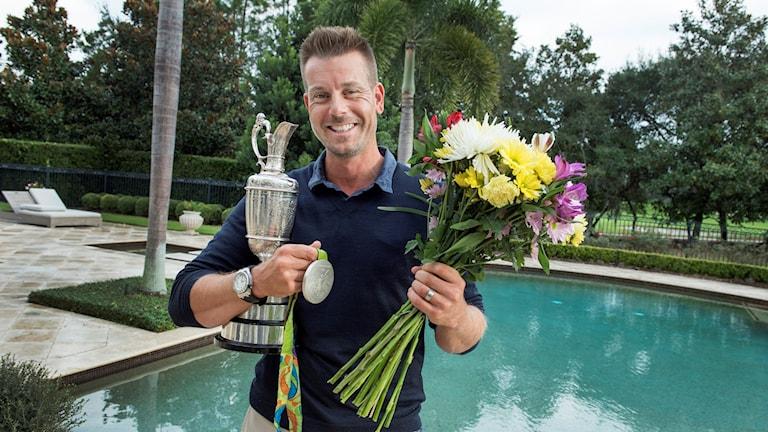 Golfspelaren Henrik Stenson ler och håller blommor, en pokal och en medalj i händerna.