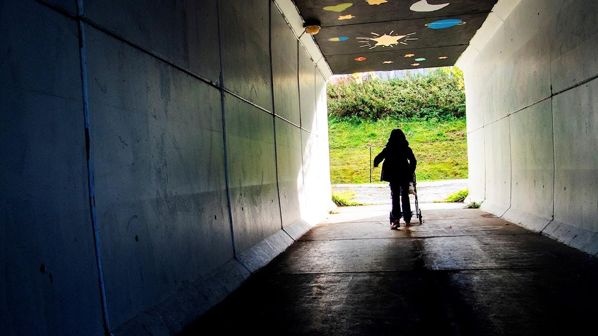 En flicka går med en dockvagn i en tunnel.