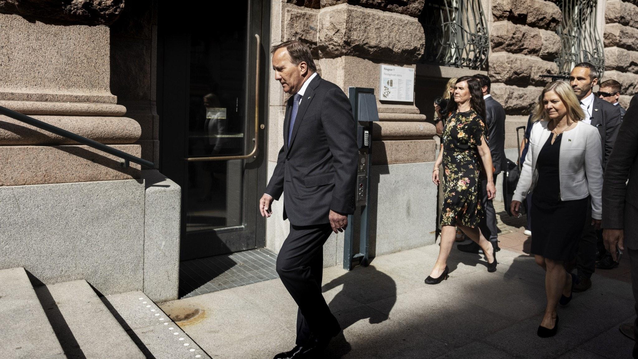 Bild på statsminister Stefan Löfven som går på en gata, med några ministrar bredvid.