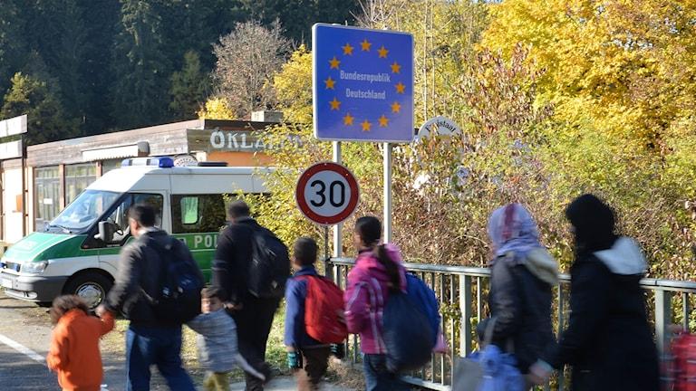 Flyktingar går över gränsen mellan Österrike och Tyskland, i oktober 2015.