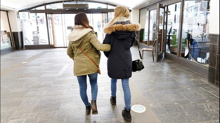Två tonårstjejer går i ett köpcentrum.