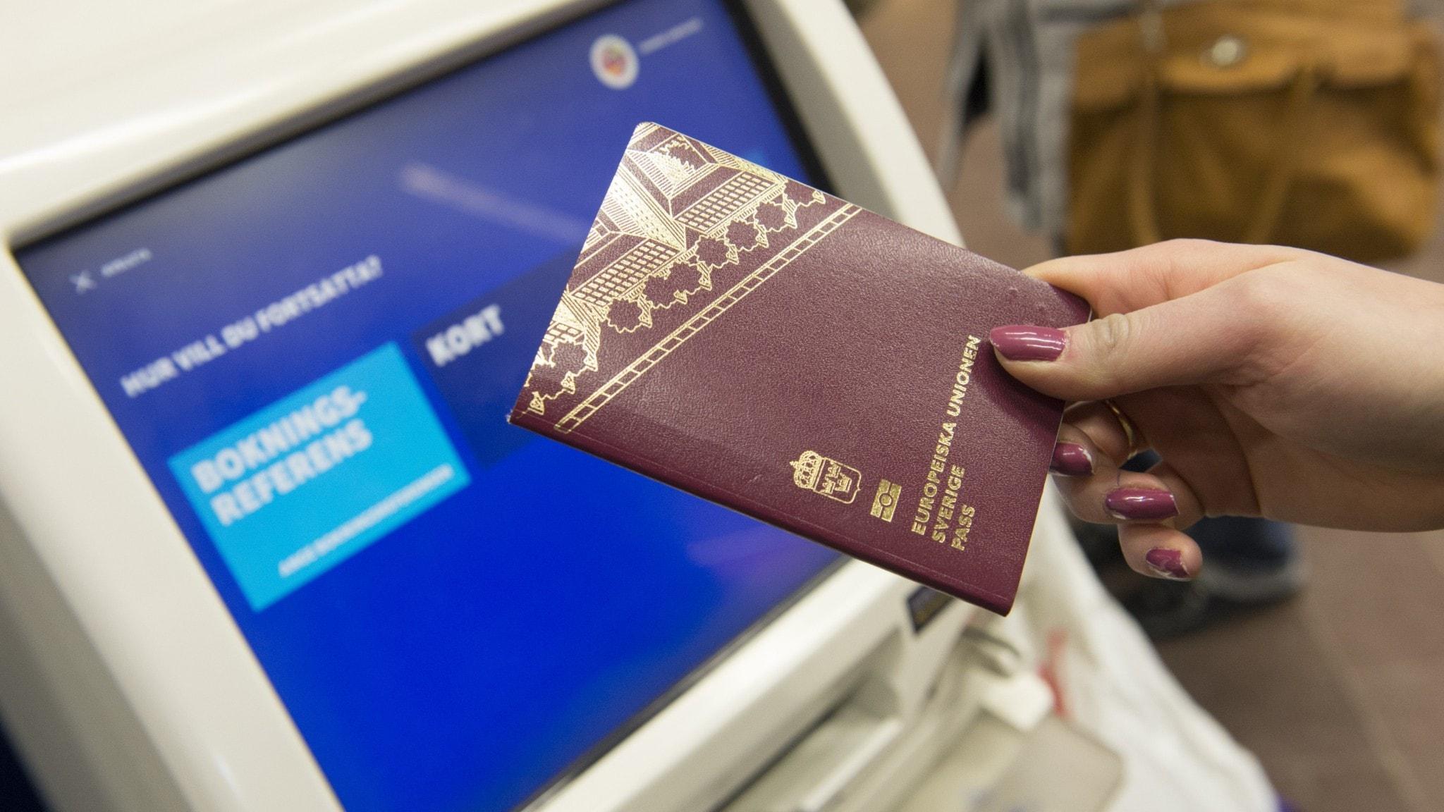 En kvinna håller upp ett pass vid incheckning på en flygplats.