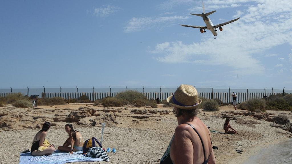 Bilden visar en kvinna på en strand som tittar upp mot ett flygplan.