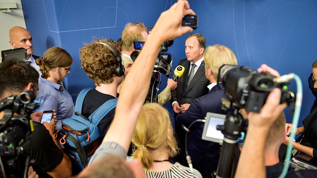 Man at the centre of a scrum of people with microphones and cameras.