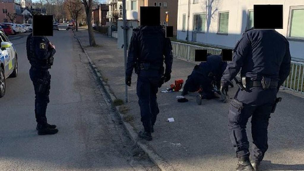 Tre poliser står runt en fjärde polis som är böjd över en man som ligger på  marken.