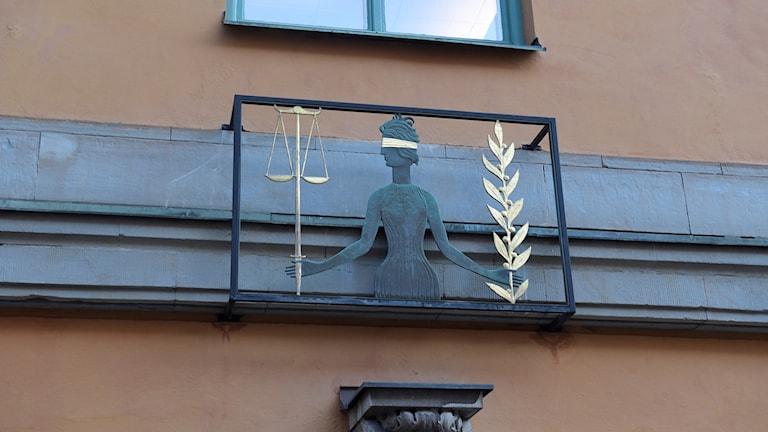 Skylt som föreställer Justitia, ovanför ingången till säkerhetssalen i Stockholms tingsrätt.