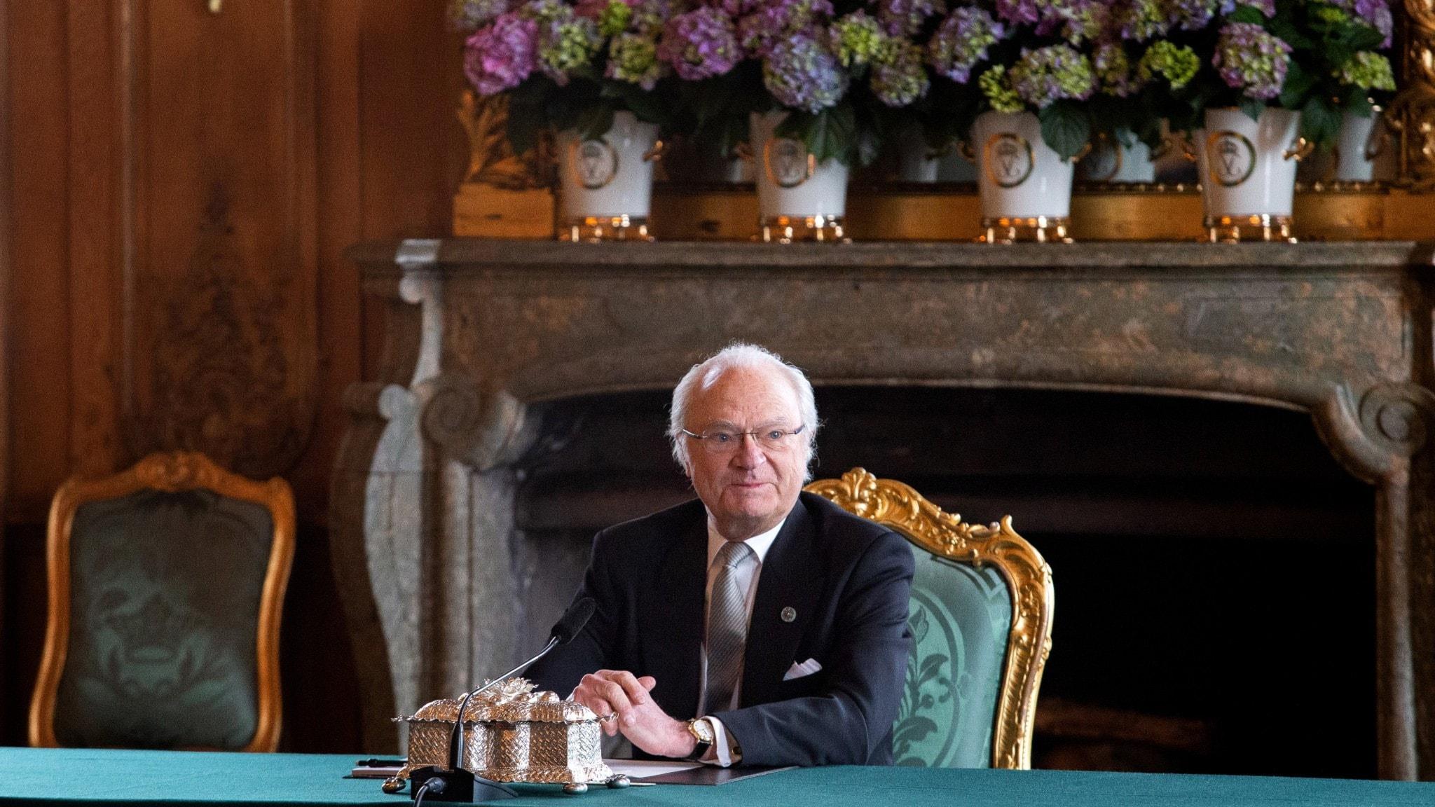 Bilden visar Sveriges kung Carl Gustaf på en stol i en stor sal med blommor och en öppen spis.