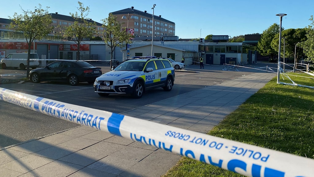 Polisavspärrningar i förgunden. Polisbilar på parkeringsplats.