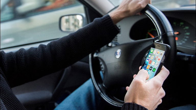 En man kör bil och använder sin mobil