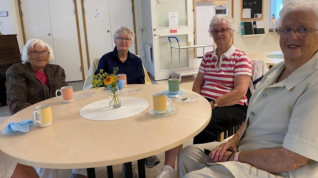Fyra kvinnor sitter vid ett bord och fikar.