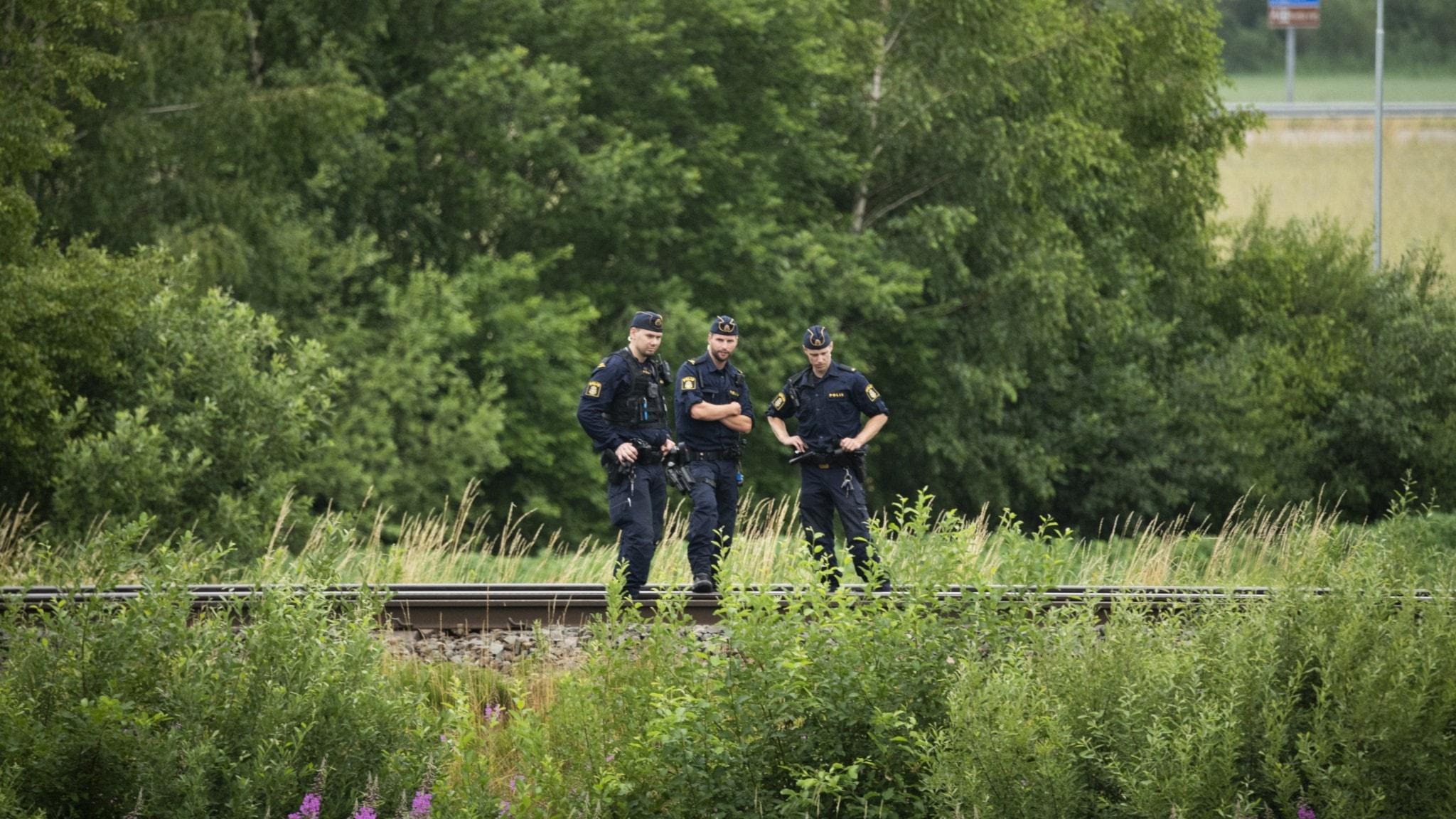 Bild på poliser som står vid ett tågspår.