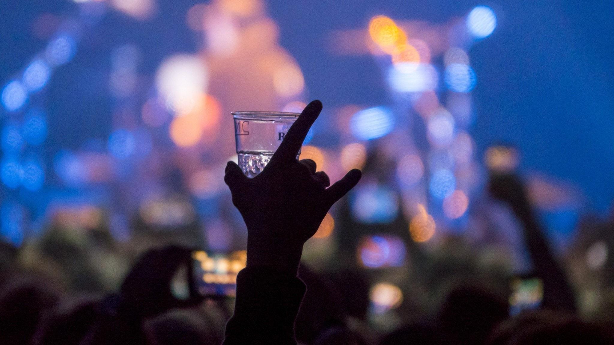 En person i en konsertpublik håller upp ett glas öl.