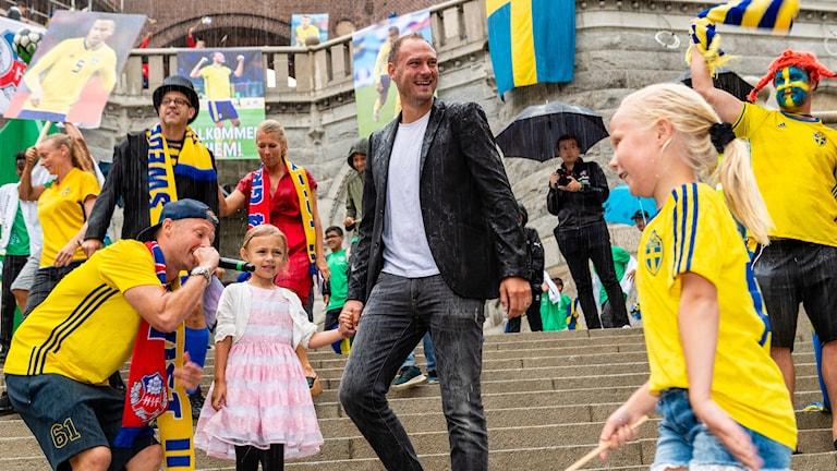 Andreas Granqvist med dottern Nova i regnet vid Terrasstrapporna i Helsingborg för att ta emot hyllningarna efter årets fotbolls-vm.