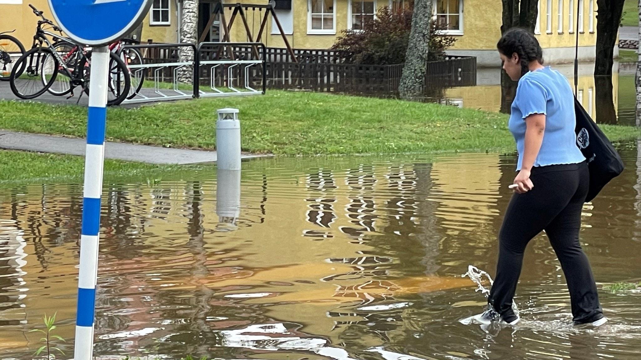 Kvinna går på översvämmat övergångsställe.