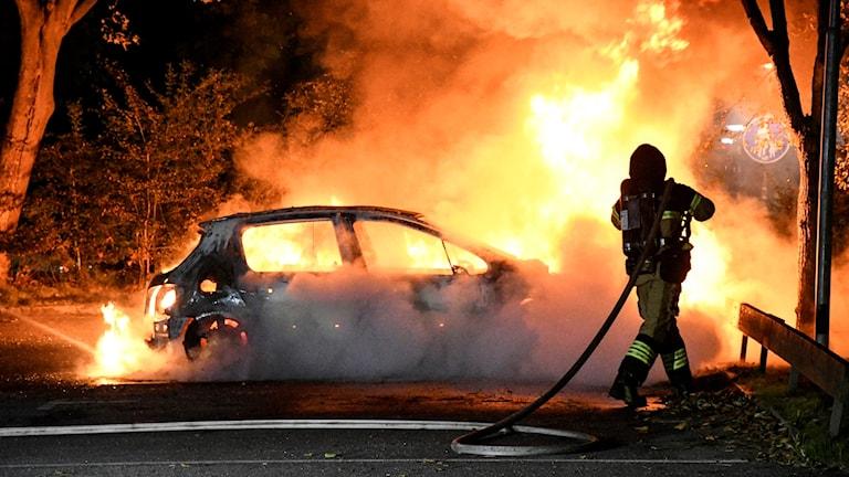 En brandman håller på att släcka en brinnande bil.