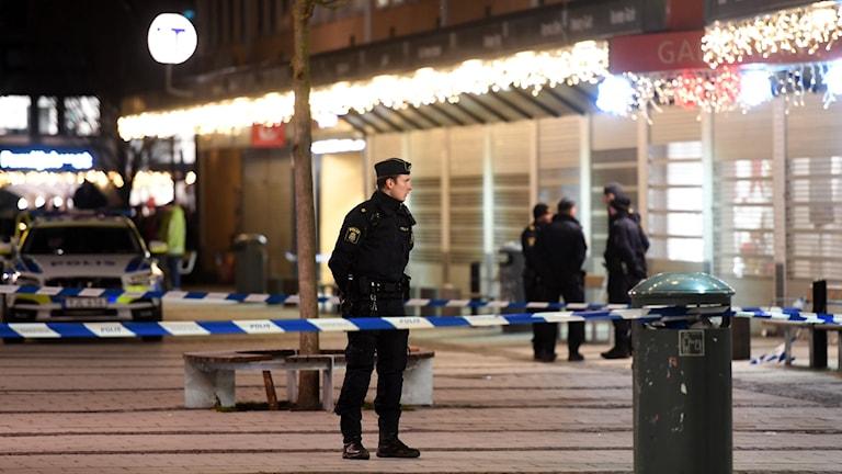 En polis och avspärrningsband utanför restaurangen på Rinkeby torg, där en man blev skjuten.
