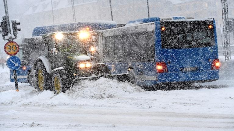 En plogbil plogar på en snöfylld gata vid Slussen i centrala Stockholm.